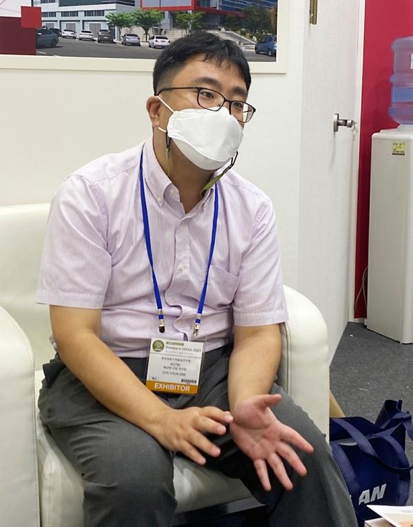 배규현 선임 연구원이 PIS KOTMI 부스에서 섬유산업 로봇에 대해 설명하고 있다.